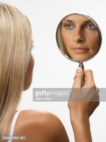 young woman looking in hand held mirror stock photo