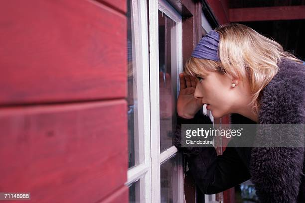 Young woman looking in house through window, side view
