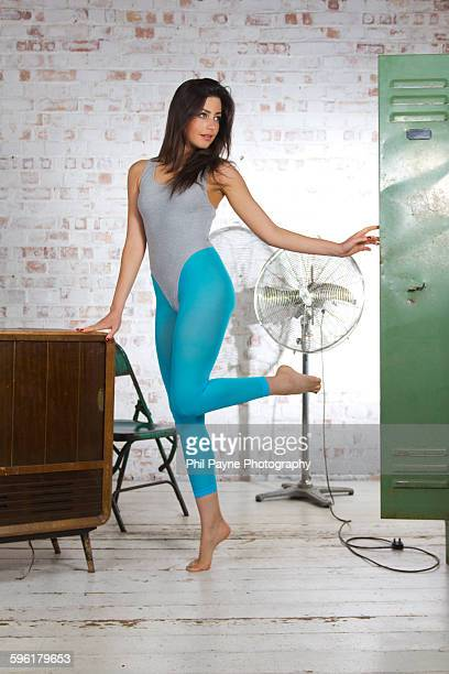 young woman looking in locker - leotard stock photos and pictures