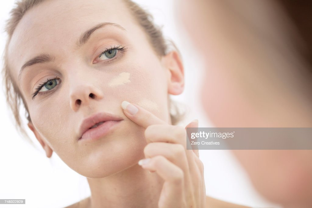 Young woman looking in mirror, applying make-up to face : Bildbanksbilder