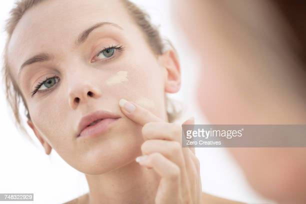 young woman looking in mirror, applying make-up to face - routine stockfoto's en -beelden