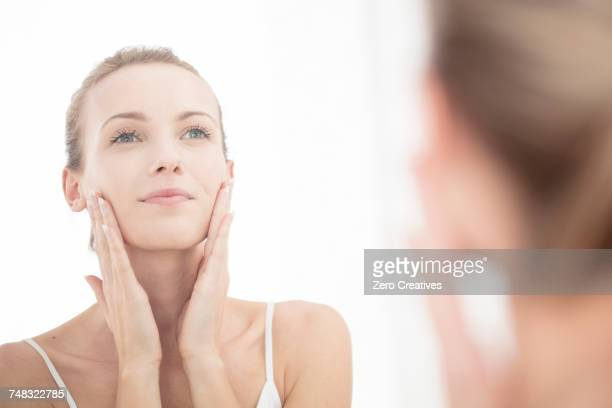 young woman looking in mirror, applying moisturiser to face - aplicando - fotografias e filmes do acervo