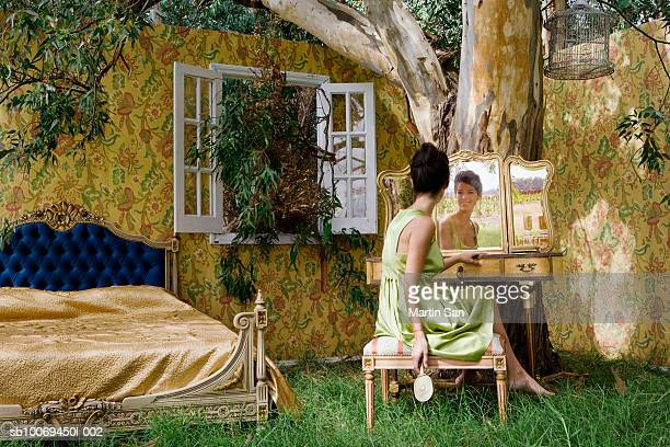young woman looking in mirror beneath tree - free walpaper stock photos and pictures