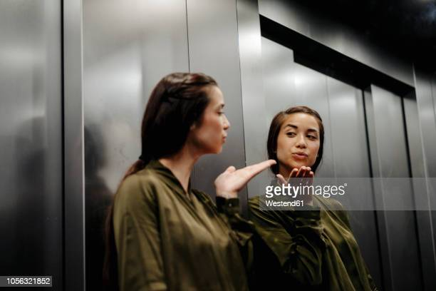 young woman looking in mirror in elevator blowing a kiss - eitelkeit stock-fotos und bilder