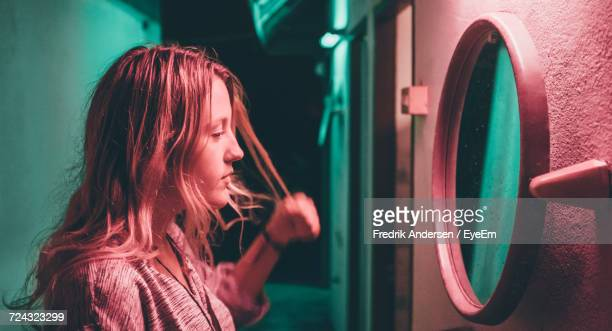young woman looking in mirror on wall of building at night - vanity mirror stock pictures, royalty-free photos & images