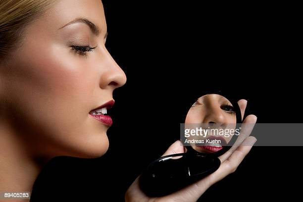 Young woman looking in mirror, portrait.