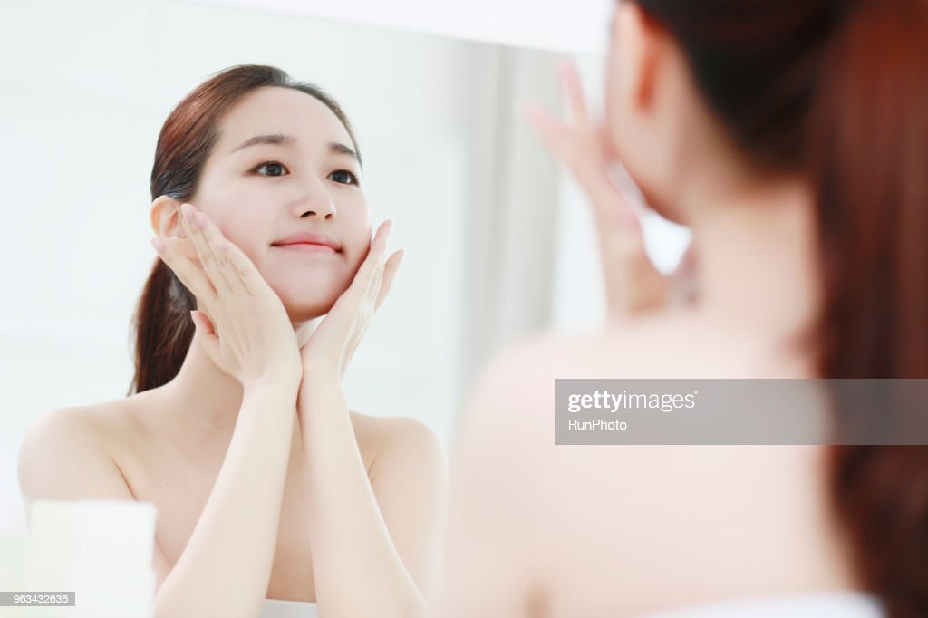 Young woman looking in mirror, touching face : Stock Photo