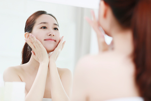 Young woman looking in mirror, touching face - gettyimageskorea