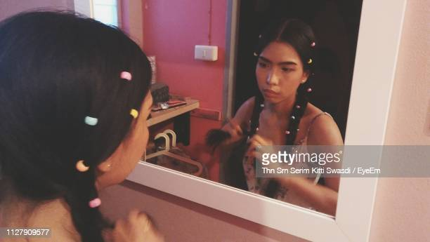 Young Woman Looking In Mirror While Braiding Her Hair At Home
