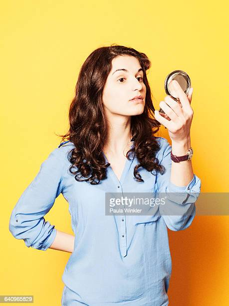 Young woman looking in powder compact mirror against yellow background