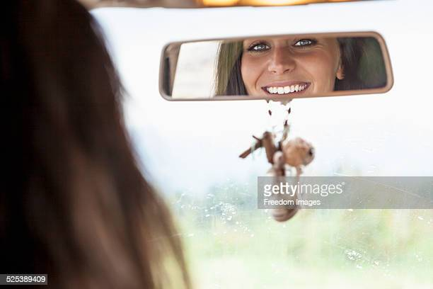 Young woman looking in rear view mirror