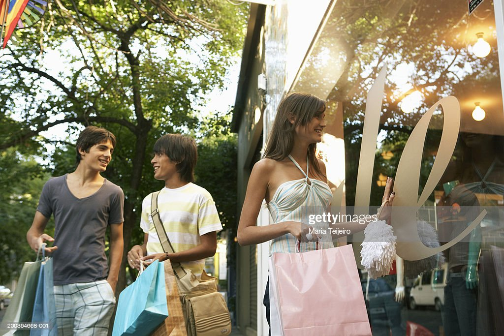 Young woman looking in shop window by two teenage boys (14-17) : Stock Photo