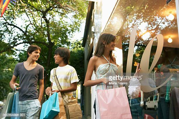 Young woman looking in shop window by two teenage boys (14-17)