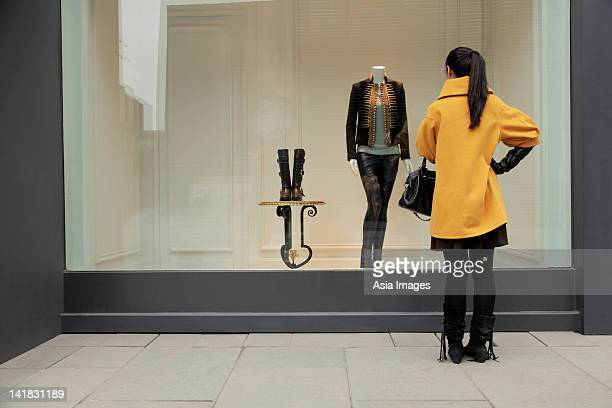 Young woman looking in shop window
