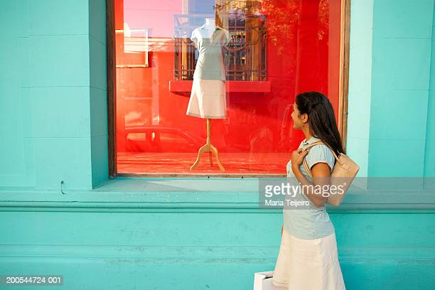 Young woman looking in shop window, side view