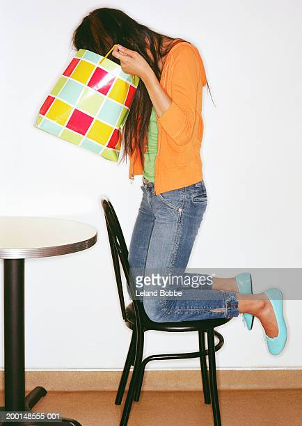 Young woman looking in shopping bag, side view