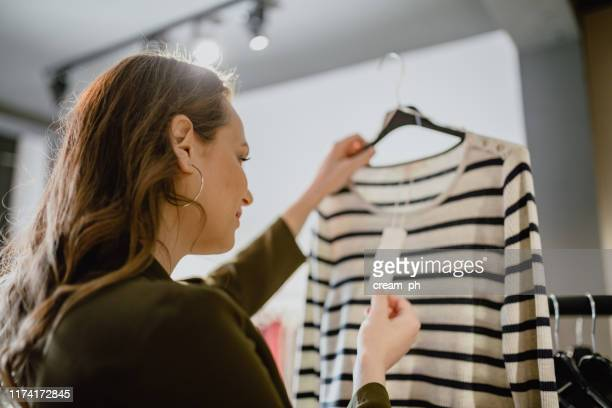 young woman looking in to price tag in the clothing store - price tag stock pictures, royalty-free photos & images