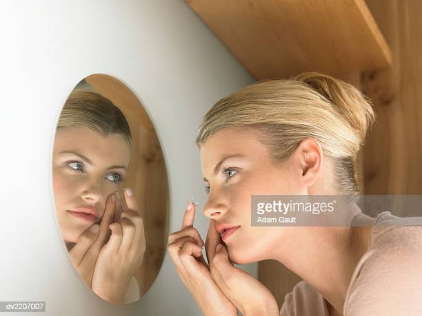 Young Woman Looking Into a Mirror and Putting on a Contact Lens