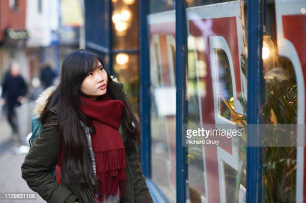 young woman looking into a store window - 欲望 ストックフォトと画像