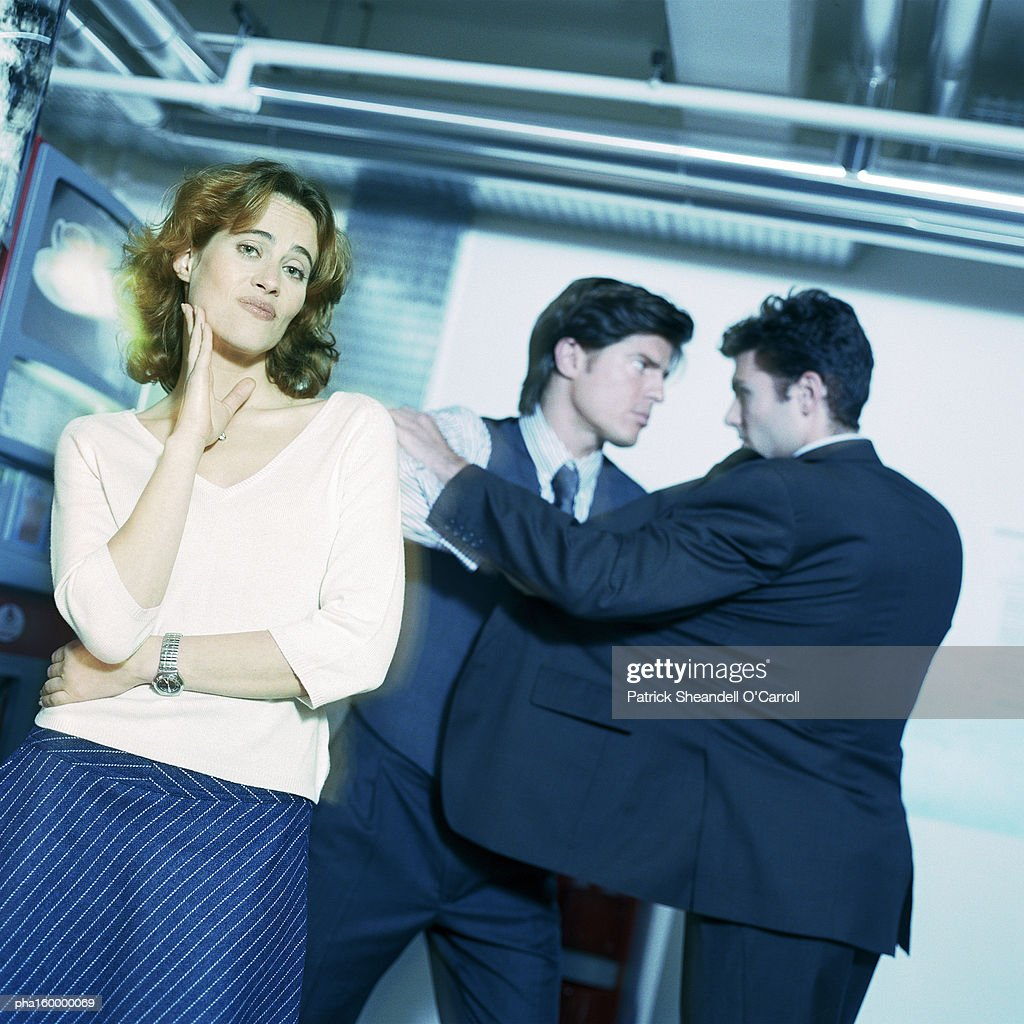 Young woman looking into camera, two men in suits face to face. : Stockfoto