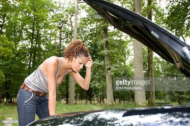 Young woman looking into hood of broken car