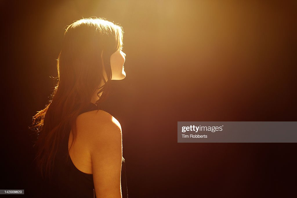 Young woman looking into light. : Stock Photo