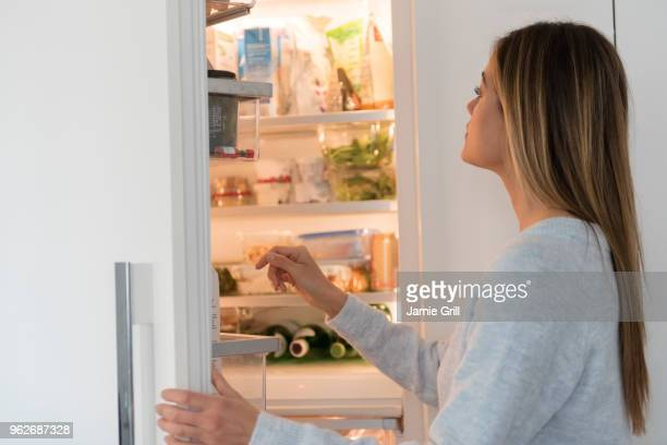 young woman looking into refrigerator - refrigerator stock pictures, royalty-free photos & images