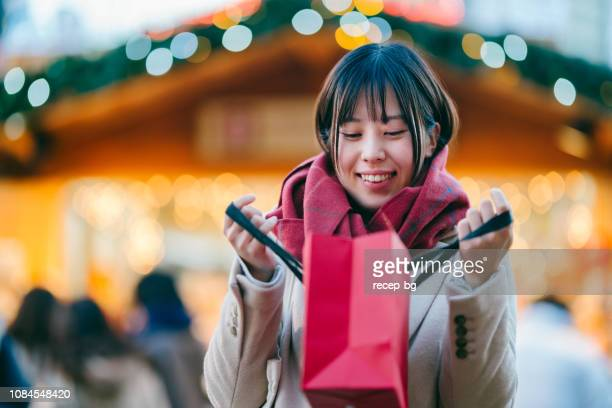 young woman looking into shopping bag excitedly - commercial activity stock pictures, royalty-free photos & images