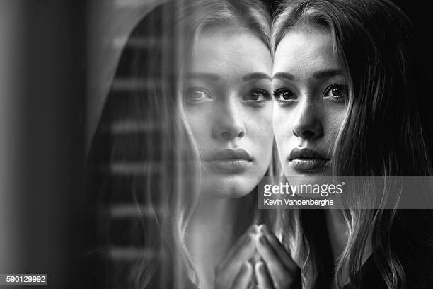 young woman looking into the camera with window reflection - spiegel stockfoto's en -beelden
