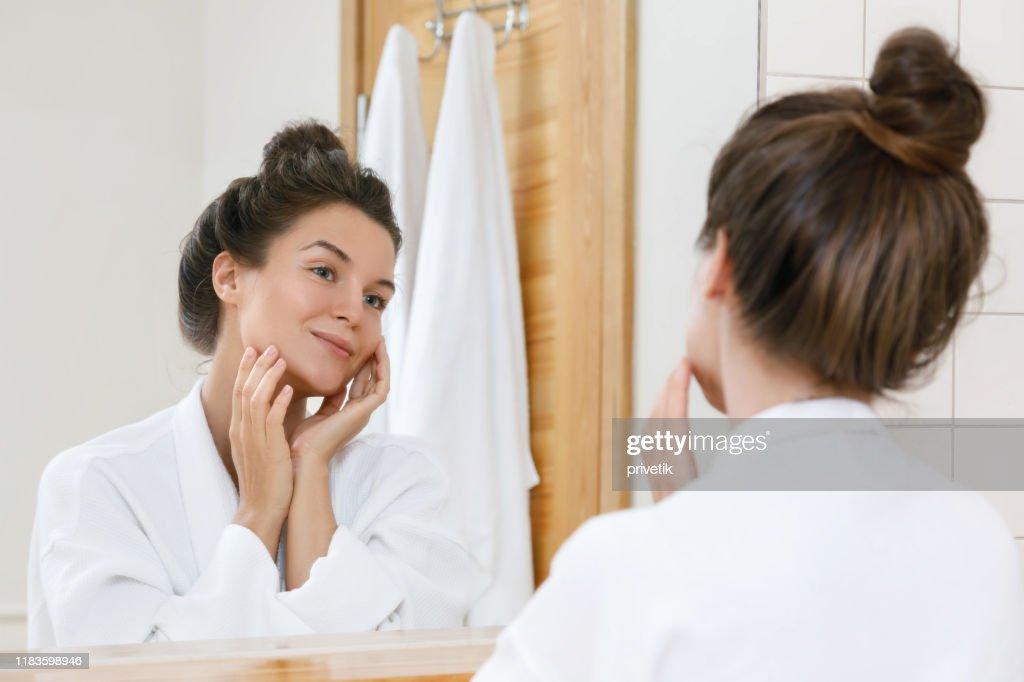 Jonge vrouw op zoek naar de spiegel : Stockfoto