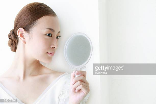 young woman looking into the mirror