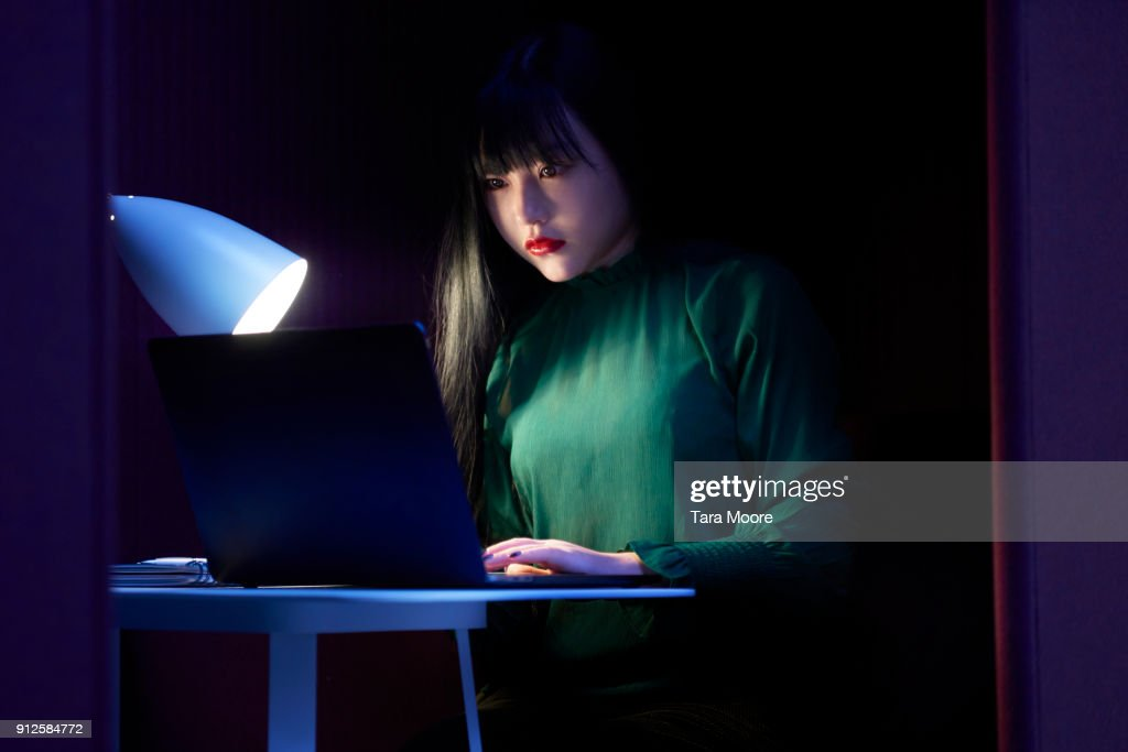 young woman looking laptop at night : Stock Photo