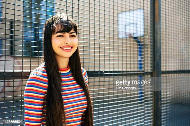 young woman looking off camera, smiling - striped shirt stock pictures, royalty-free photos & images