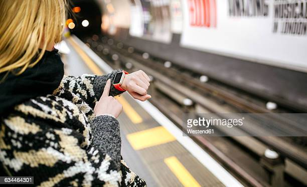 Young woman looking on her smartwatch waiting for the subway