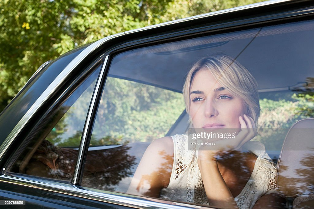 Young woman looking out a car window : Photo