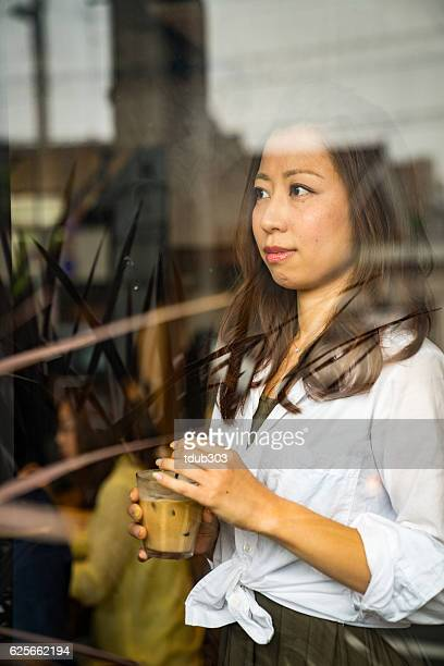 Young woman looking out cafe window with a coffee