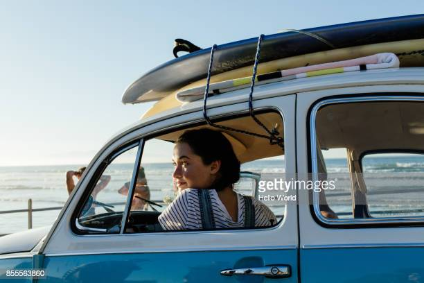 young woman looking out car window, surfboards on roof - old car stock pictures, royalty-free photos & images