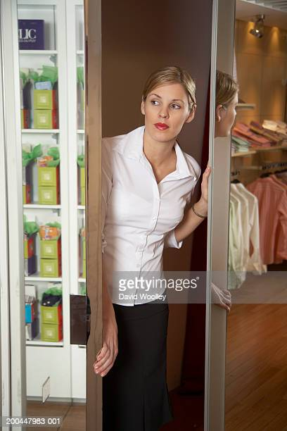 young woman looking out from between mirrored doors in clothes store - open blouse stock photos and pictures