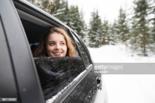 Young woman looking out of a car window in winter landscape