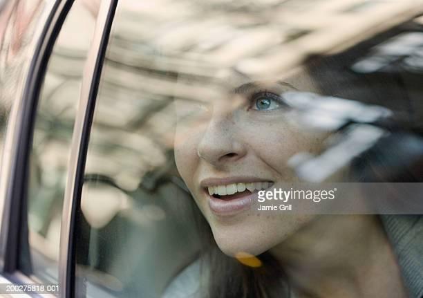 young woman looking out of car window, smiling - regarder par la fenêtre photos et images de collection