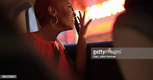 Young woman looking out of taxi window at night