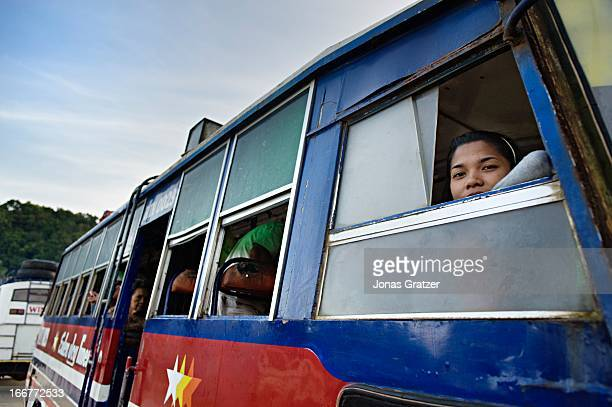 Young woman looking out of the window of a bus on the way to Puerto Princesa City. PARTIAL MODEL RELEASE.