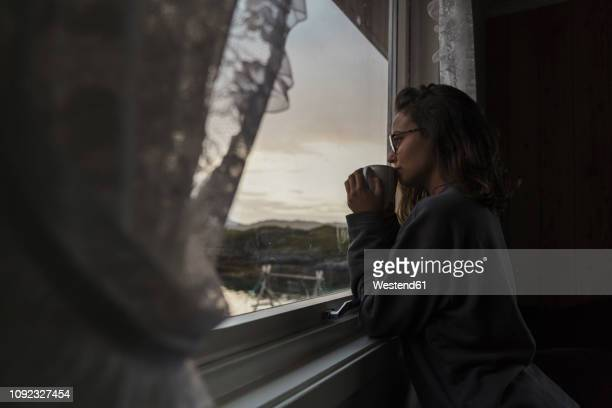 young woman looking out of window, drinking tea - verdriet stockfoto's en -beelden
