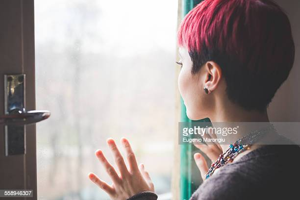 Young woman looking out of window, hands touching window, rear view