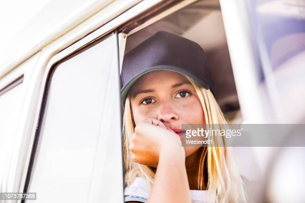 young woman looking out of window of a van - baseball cap stock pictures, royalty-free photos & images
