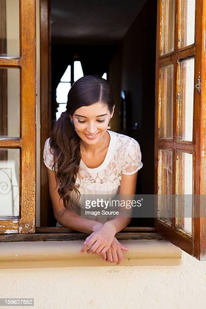 young woman looking out of window - appoggiarsi foto e immagini stock