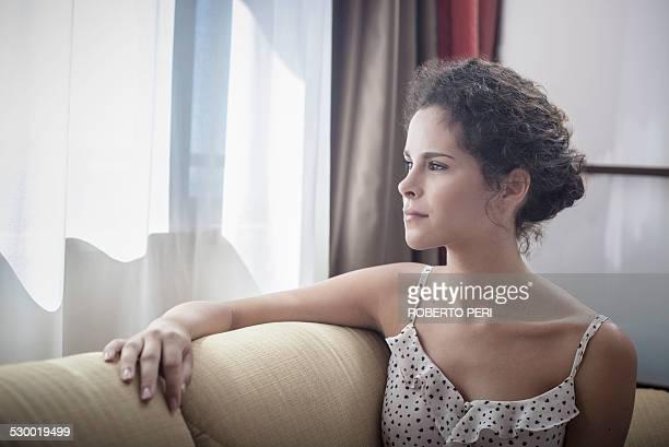 young woman looking out of window - roberto ricciuti foto e immagini stock