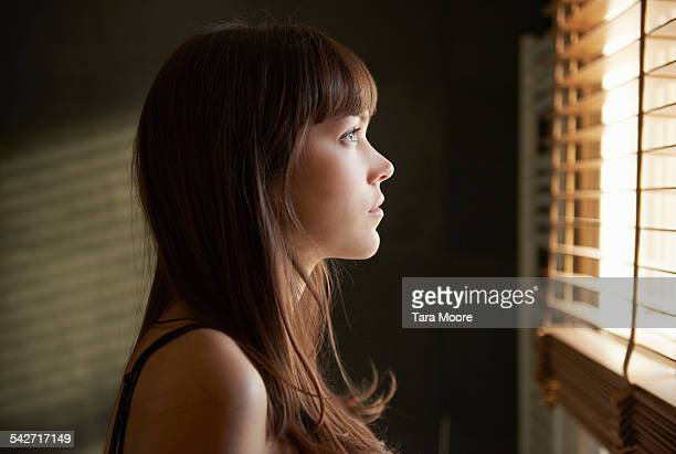 young woman looking out of window - brown eyes stock pictures, royalty-free photos & images