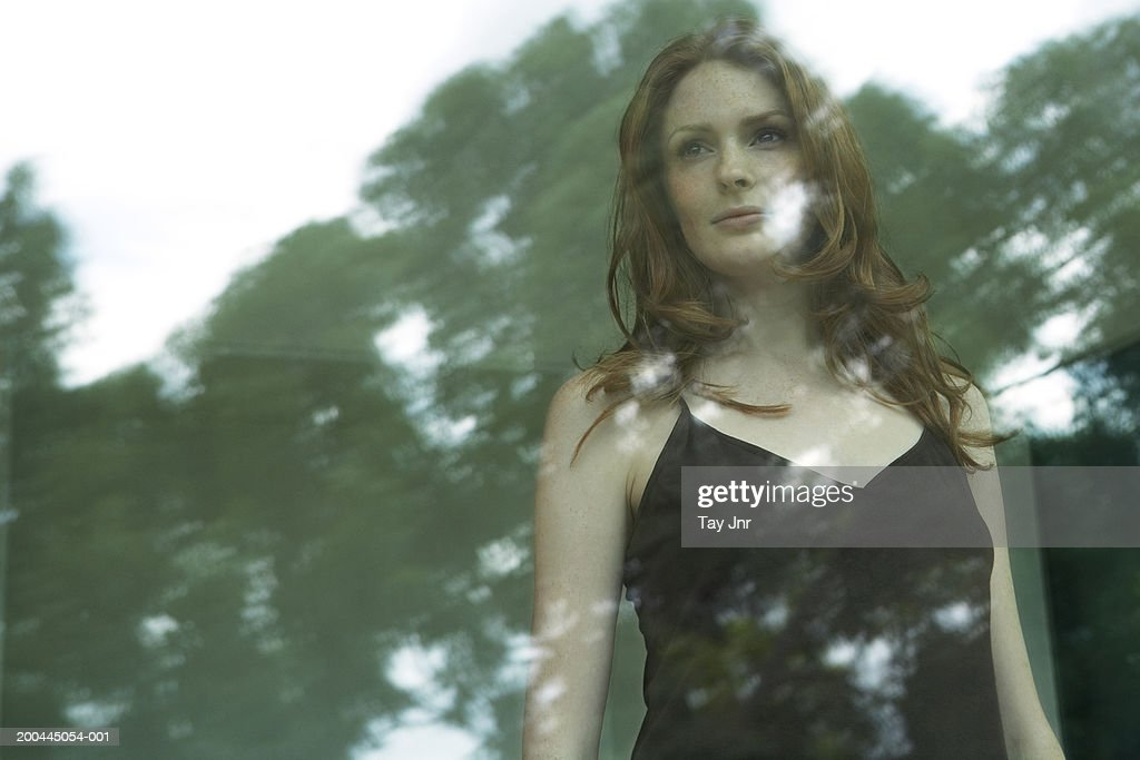 Young woman looking out of window, trees reflected in glass : Stock Photo