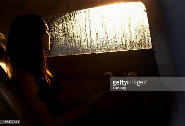Young woman looking out the window of the car and contemplating on a rainy night in Beijing